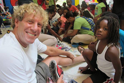 Billy4Kids Founder and iPark CEO Billy Lerner helping fit shoes on children
