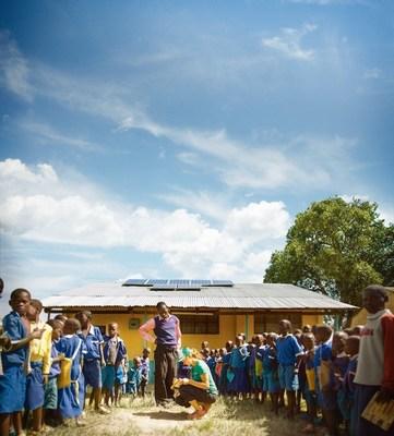 SolarCity photovoltaic designer Alex Webster explains solar energy to students at Kulumbeni Primary School in Matate, Kenya.