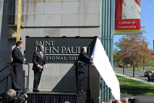 """New name for the new saint.  Knights of Columbus Deputy Supreme Knight Logan Ludwig unveils a new sign for the Saint John Paul II National Shrine in Washington D.C. with the help of Shrine Director Patrick Kelly and the Rev. Gregory Gresko, shrine chaplain. Formally the shrine of Blessed John Paul II, the name upgrade followed by just a few hours the canonization of Pope John Paul, along with that of Pope John XXIII, in Rome. It is among the first places in the world to bear the name of """"St John Paul II."""" (PRNewsFoto/Knights of Columbus)"""