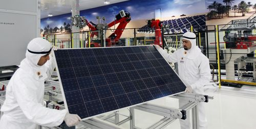 Two Qatar Solar Energy technicians handle a solar panel (PRNewsFoto/QATAR SOLAR ENERGY)