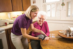 Home Instead CAREGiver(SM) puts wrist brace on senior with arthritis. (PRNewsFoto/Home Instead Senior Care)