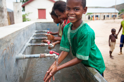 Julien, 12, washes his hands in clean water from newly installed taps at Ampanasana primary school in ...