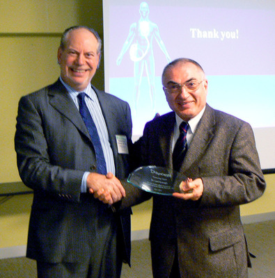 SynCardia Chairman/CEO/President Michael Garippa congratulates Dr. Latif Arusoglu, who was honored with a Proctoring Impact Award from SynCardia at ISHLT for his tireless efforts in proctoring first implants of the Total Artificial Heart at hospitals around the world.  (PRNewsFoto/SynCardia Systems, Inc.)