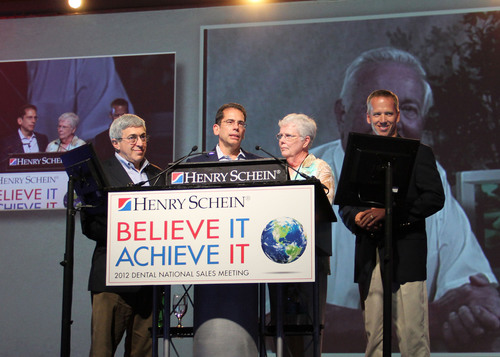 Stanley Bergman, Chairman and CEO, Henry Schein; Jim Breslawski, President and COO, Henry Schein; Judy Sullivan; and Tim Sullivan, President, Henry Schein Dental, remember the late Bob Sullivan (pictured behind on screen) as Henry Schein celebrated the 15th anniversary of the Sullivan Dental - Henry Schein merger during the company's Dental National Sales meeting.  (PRNewsFoto/Henry Schein, Inc.)