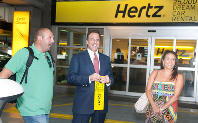 Mark Frissora, Hertz Chairman & CEO, center, celebrates 25,000th Dream Cars rental by surprising customers Mike Yonover and Marissa Yonover on Wednesday, Sept. 3, 2014 in Miami. (Mitchell Zachs/AP Images for Hertz)