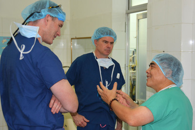 From l., AOFAS volunteers Thomas A. McDonald, MD, and Mark P. Slovenkai, MD, consult with Ngo Toan, MD, chair of orthopaedics at Viet Duc Hospital in Hanoi. (Photo: Paul Docktor, MD, Denver)