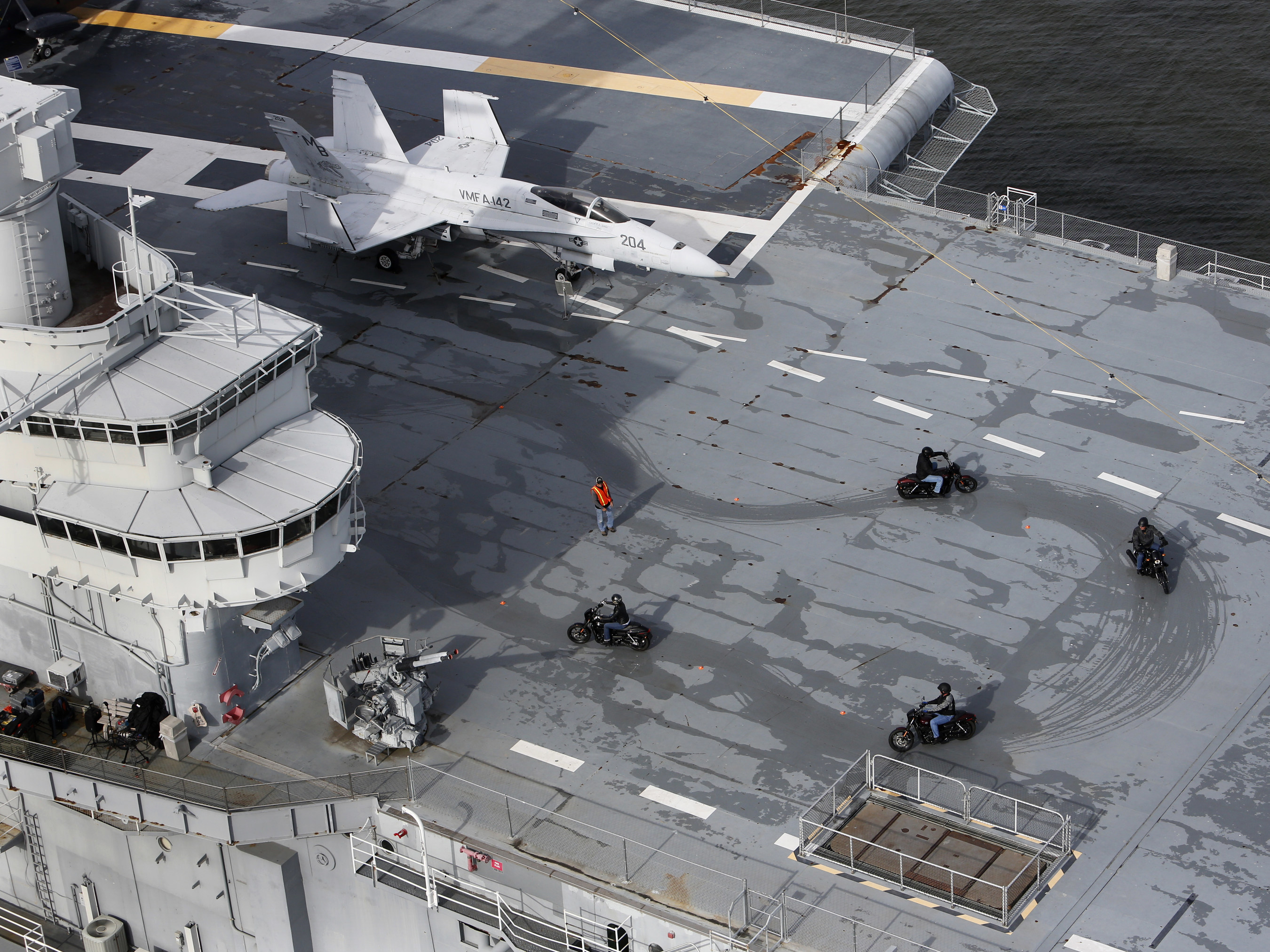 The scene from above the flight deck of the USS Yorktown -- six veterans and active-duty military ride the H-D Street 500 as Harley-Davidson announced it is offering current and former U.S. military free Riding Academy motorcycle training in Mt. Pleasant, S.C., Thursday, May 7, 2015. (Mic Smith/AP Images for Harley-Davidson)