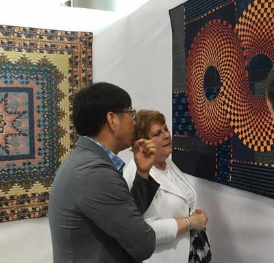 """Two quilts from The Collection of The National Quilt Museum at The Woljean Museum, Incheon Korea. In front: """"Infinity"""" by Nancy Ota. In back, """"Tulips Aglow"""" by Mary Kay Hitchner."""
