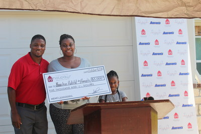 (L to R): Warrick Dunn, Terorah Davis, and daughter Londyn Davis pose in front of the family's new, fully-furnished home made possible thanks to furniture and electronics donations from Aaron's (www.aarons.com). Warrick Dunn Charities' Homes for the Holidays assists single parents in becoming first-time homeowners by providing the materials necessary for long-term stability and the provisions required to ensure that both parent and children can thrive educationally, socially and economically. Aaron's has been a longtime supporter of Warrick Dunn Charities initiatives and began contributing home furnishings, appliances and electronics to the Homes for the Holidays program in 2003.
