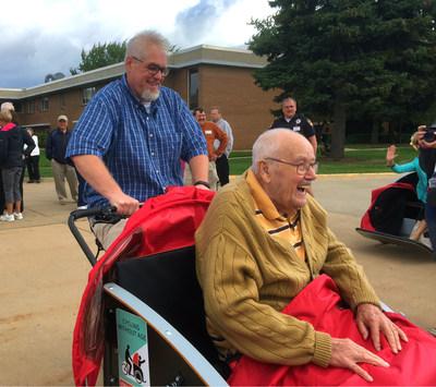 Local Oshkosh resident Jon Uecker drives Lutheran Homes of Oshkosh elder Jim on the rickshaws during the Cycling Without Age kickoff event in Oshkosh, Wisconsin.