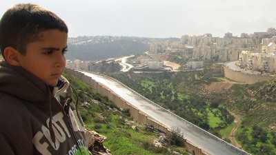 Young Gibreel Burnat looks over the Israeli settlements that surround his family's home town of Bil'in in a scene from the Oscar® -nominated documentary 5 BROKEN CAMERAS, co-directed by his father, Emad Burnat, and Guy Davidi. A Palestinian-Israeli-French co-production. A Kino Lorber Release.