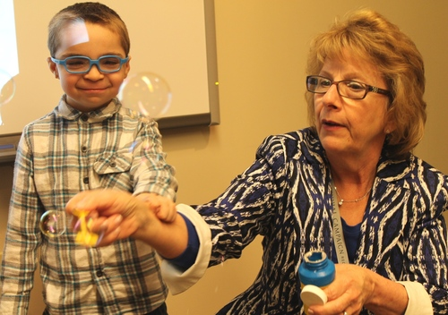 Barbara Haas-Givler, M.Ed., BCBA, trainings and consultative services/behavior consultant, ADMI, blows bubbles with 5-year-old patient Kaleb Miller during a recent visit to the Geisinger-Bucknell Autism & Developmental Medicine Center in Lewisburg, Pa. (PRNewsFoto/Geisinger Health System)