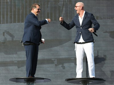 """Frank Del Rio and Pitbull celebrate with onstage """"fist bump"""" at the Norwegian Escape christening ceremony."""