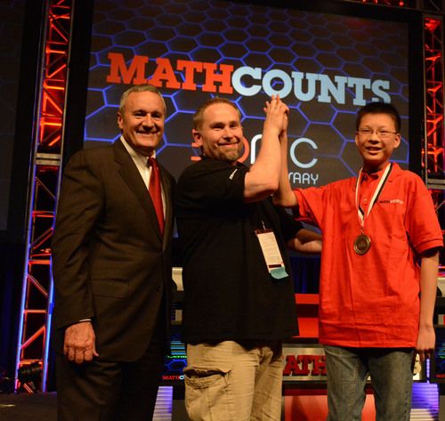 Raytheon Chairman and CEO William H. Swanson (left) congratulates Alec Sun, an 8th-grader from Lexington, ...