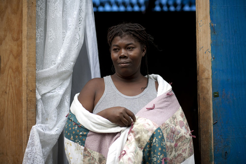 Claudette Gaston, in front of her temporary shelter, wraps herself in the quilt she received from Lutheran ...
