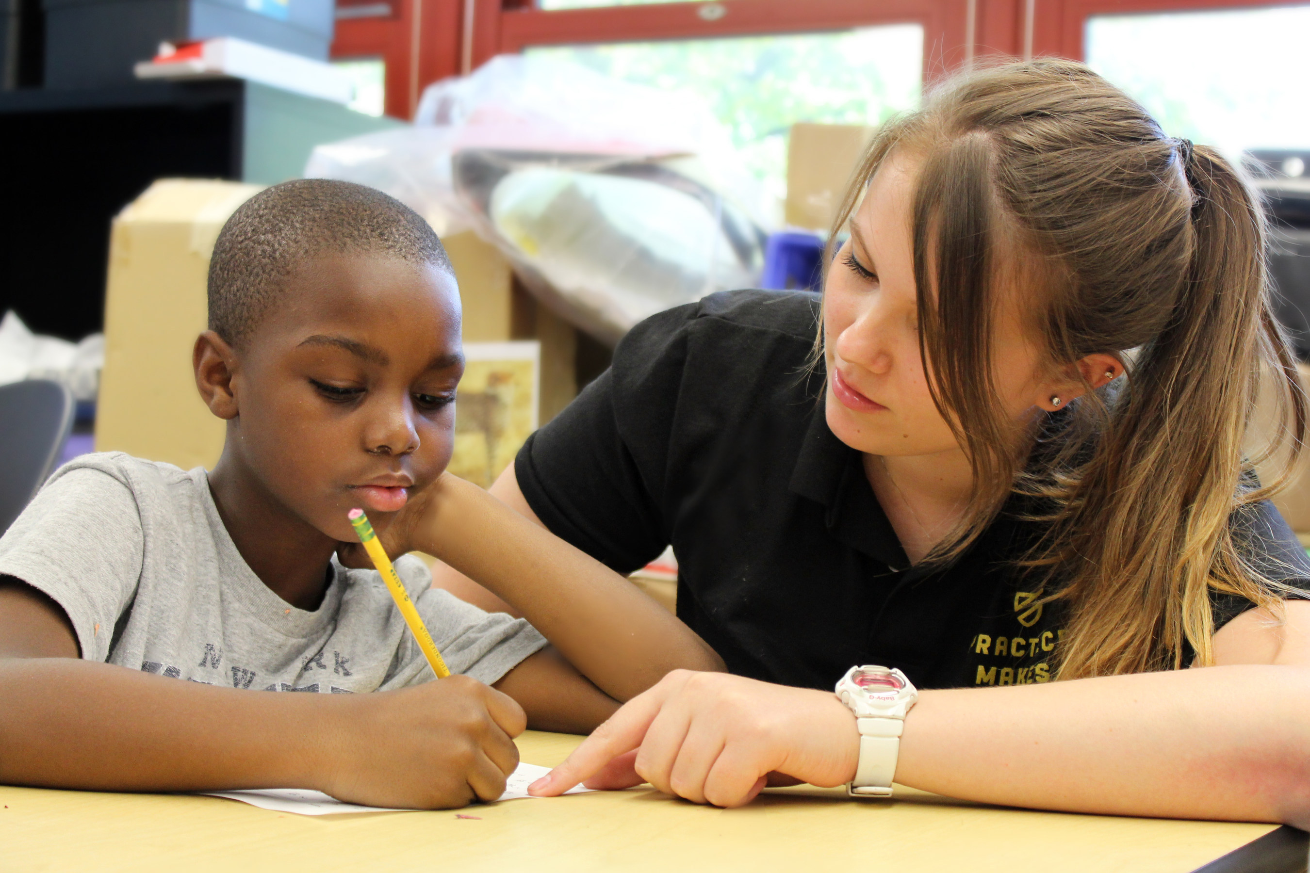 A Practice Makes Perfect Teaching Fellow works with a student from TFOA - Professional Preparatory Charter ...