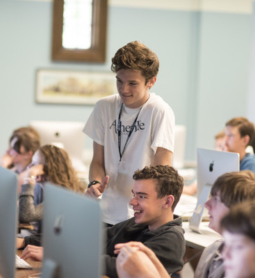 "Gabriel Wong, a 14-year-old Asheville School student from the Bahamas, shares a moment with Georgia Tech student Jack Hamilton (standing) during Asheville School's App Development Summer Camp. Wong created his own app, ""Go Switchy,"" weeks after attending the app camp. Asheville School is one of the first schools in the country to integrate Apple's Swift programming language into its academic and extracurricular program."