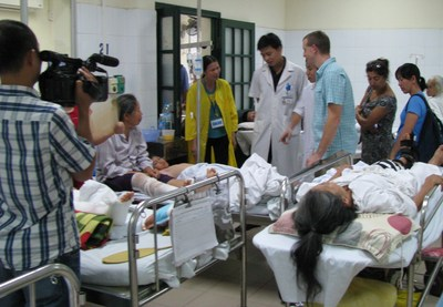AOFAS volunteer Aaron Guyer, MD (blue shirt) meets with patients in recovery at Viet Duc Hospital in Hanoi, Vietnam. The same day, a local television station sent a camera crew to film the AOFAS volunteers' work. (PRNewsFoto/AOFAS)