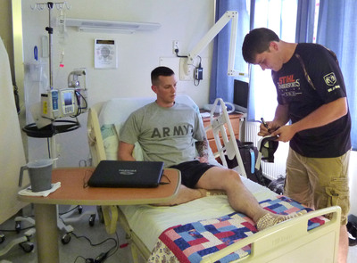 STIHL® TIMBERSPORTS® United States 2013 Lumberjack Champion Matt Cogar signs an autograph for a U.S. soldier patient during his visit to the largest military hospital outside of the continental U.S., the USO Warrior Center at Landstuhl Regional Medical Center, Germany on Aug. 6, 2013. Cogar, age 26 of Diana, W. Va., will return to Germany Oct. 25-26 to represent the United States in the STIHL TIMBERSPORTS World Championship in Stuttgart. (PHOTO CREDIT: U.S. Army Photo/Chuck Roberts)