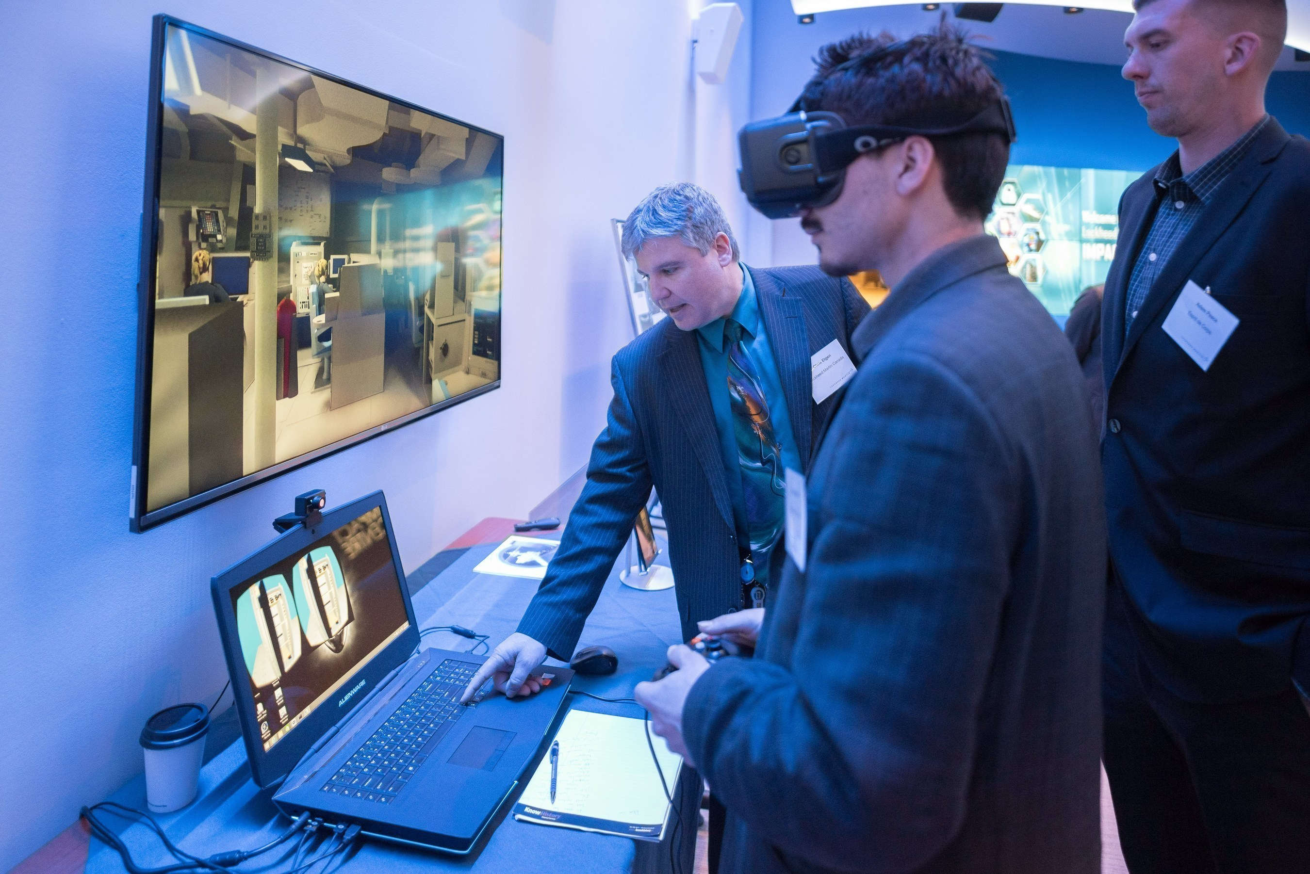 A member of the Lockheed Martin team demonstrates virtual reality goggles at the IMPACT Centre grand opening.