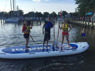 Injured veterans pose after winning the monster stand-up paddleboarding competition at a program gathering with Wounded Warrior Project in Middle River, Maryland.