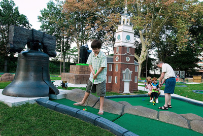 A family plays Philly Mini Golf at Franklin Square, one of the city's original parks. Run by Historic Philadelphia, Inc., the landmark is also home to the Philadelphia Park Liberty Carousel and two playgrounds.  (PRNewsFoto/Greater Philadelphia Tourism Marketing Corporation)