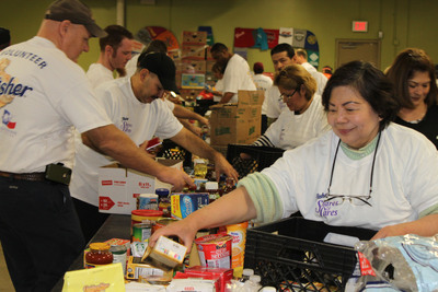 "More than 35 local employees from the Fisher Nuts plant in Selma, Texas packed up holiday meals for families in need at the San Antonio Food Bank as part of the Fisher ""Shares & Cares"" Campaign.  (PRNewsFoto/Fisher Nuts)"