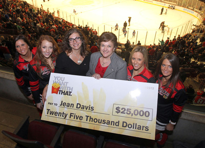 """McDonald's presents """"You Want McDonald's Fries With That"""" contest winner, Jean Davis of Mt. Pulaski, IL, a $25,000 check at the Chicago Blackhawks hockey game on February 23, 2012.  (PRNewsFoto/McDonald's)"""