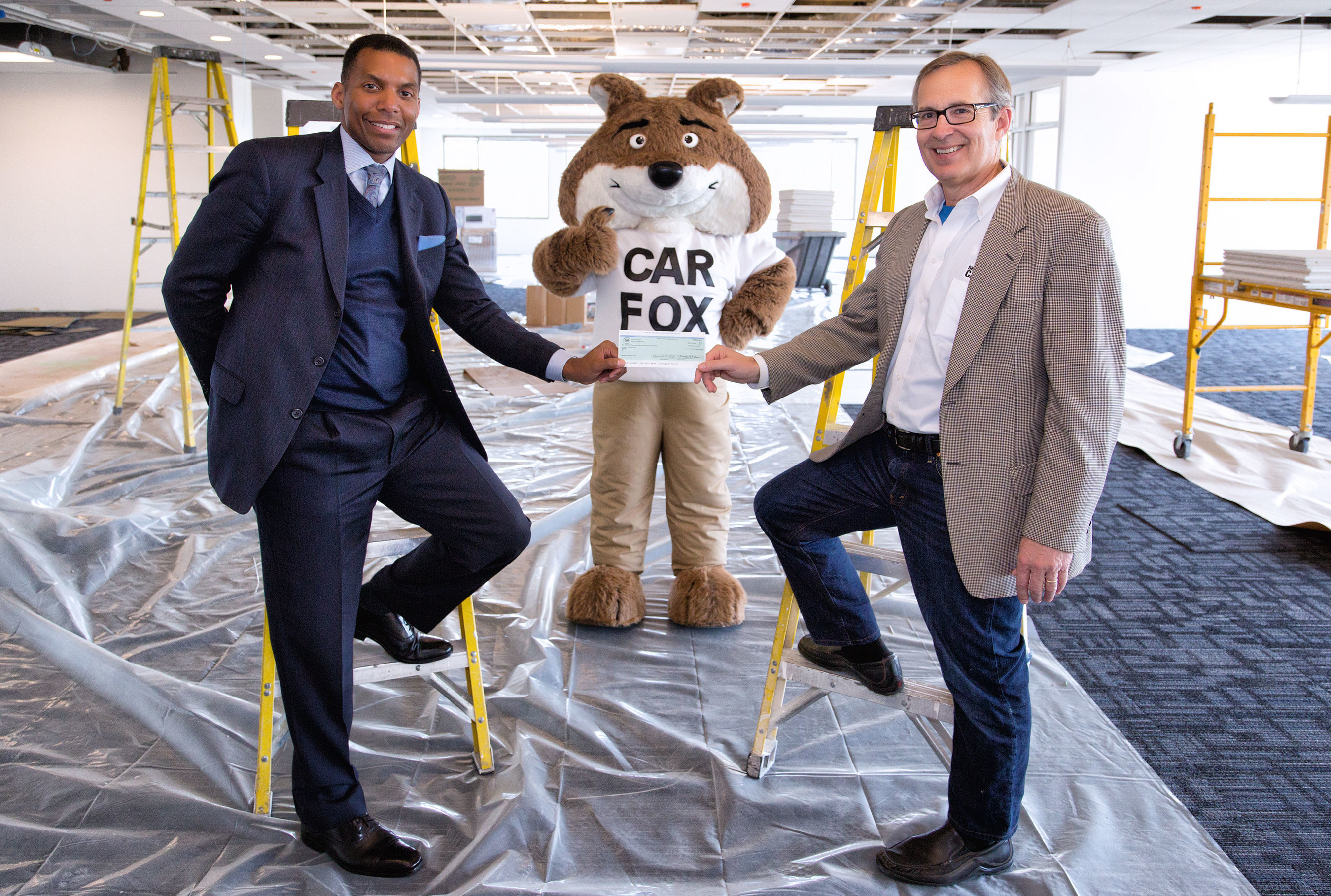 Rodney Lusk, left, from Fairfax County Economic Development Authority presents Carfax president Dick Raines with a $150,000 grant towards the expansion of Carfax headquarters in Centreville, Va.