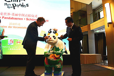 Li Jinzao, chairman of the China National Tourism Administration, and Jochen Szech, president of the Alliance of Independent Travel Traders, added the finishing touches to the eyes of the panda serving as the mascot to the event.