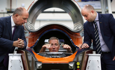 Driver Andy Green sits in the cockpit of Bloodhound SSC as he explains the controls to Frank Klaas, Director of International Communications for Zhejiang Geely Holding Group (ZGH), (left) and Ash Sutcliffe, (right) PR Manager for ZGH. (PRNewsFoto/The BLOODHOUND Project)
