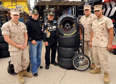 NASCAR driver Ryan Newman (second from left) of the #39 U.S. Army car and his team tire specialist, Jet  Zarrella, take the time to pose for a photo with Lance Corporal Thomas J. Case, Master Sergeant James E. Starr and Corporal Mark Anthony Feuntes of the U.S. Marine Corps after receiving special Goodyear Support Our Troops tires from the Marines.  Goodyear, exclusive tire supplier of NASCAR's three major national series and NHRA Racing's Top Fuel and Funny Car series, is honoring and supporting U.S. Armed Forces by transforming the appearance of all related racing tires over the September 16th weekend. This marks the second straight year that Goodyear has altered the sidewalls of its race tires to honor U.S. troops.