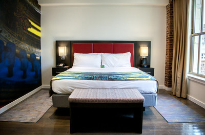The Hotel Indigo Newark Downtown is located in the historic National State Bank Building, and features exposed brick in the rooms dating back to 1912. Rooms also feature plush bedding, hard-surface flooring with area rugs and a nod to Thomas Edison's work through the mural and bed throw, seen here.