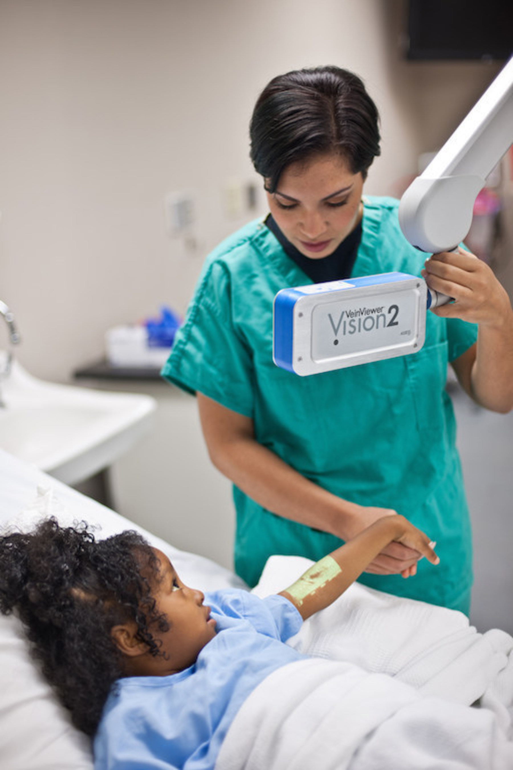 A nurse treats a pediatric patient using vein illumination technology VeinViewer Vision2 (PRNewsFoto/Christie Medical Holdings, Inc.)