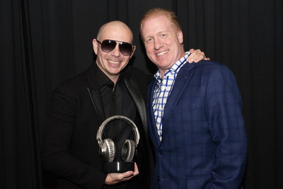 SoundExchange President and CEO Michael Huppe (R) presents Pitbull with its Digital Radio Award prior to the artist's concert in Washington, D.C., on August 4. SoundExchange honors recording artists with its Digital Radio Award once they amass more than one billion streams on the 2,500 digital radio services with whom they partner. (Photo by Chris Williams for SoundExchange).