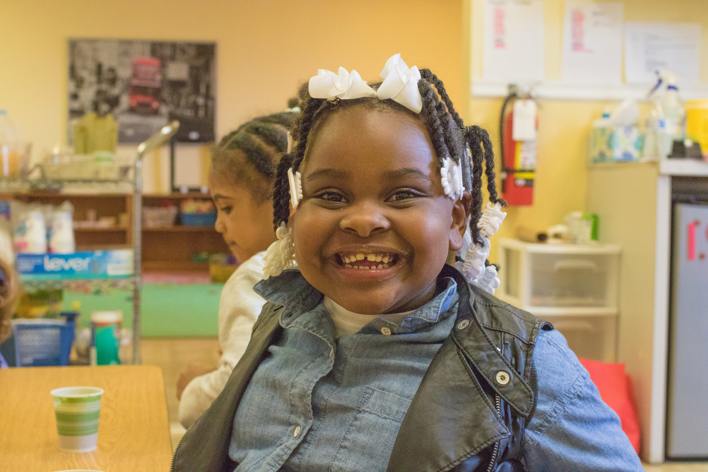 """Adonai, 4, says she loves chocolate, but she also loves apples, carrots, and strawberries. """"Pink is my favorite."""" Her grandma, who she calls """"grammy,"""" came early to pick her up, but let her stay a little bit longer for the smoothies. """"It's good!"""" she tells grammy, who is sampling the smoothies. In collaboration with Alpha Montessori School at the YWCA in Flint, Mich., Save the Children is piloting a smoothie program to get children to eat healthy, nutrient-rich foods to mitigate the impact of lead exposure. Photo by Stuart Sia / Save the Children."""