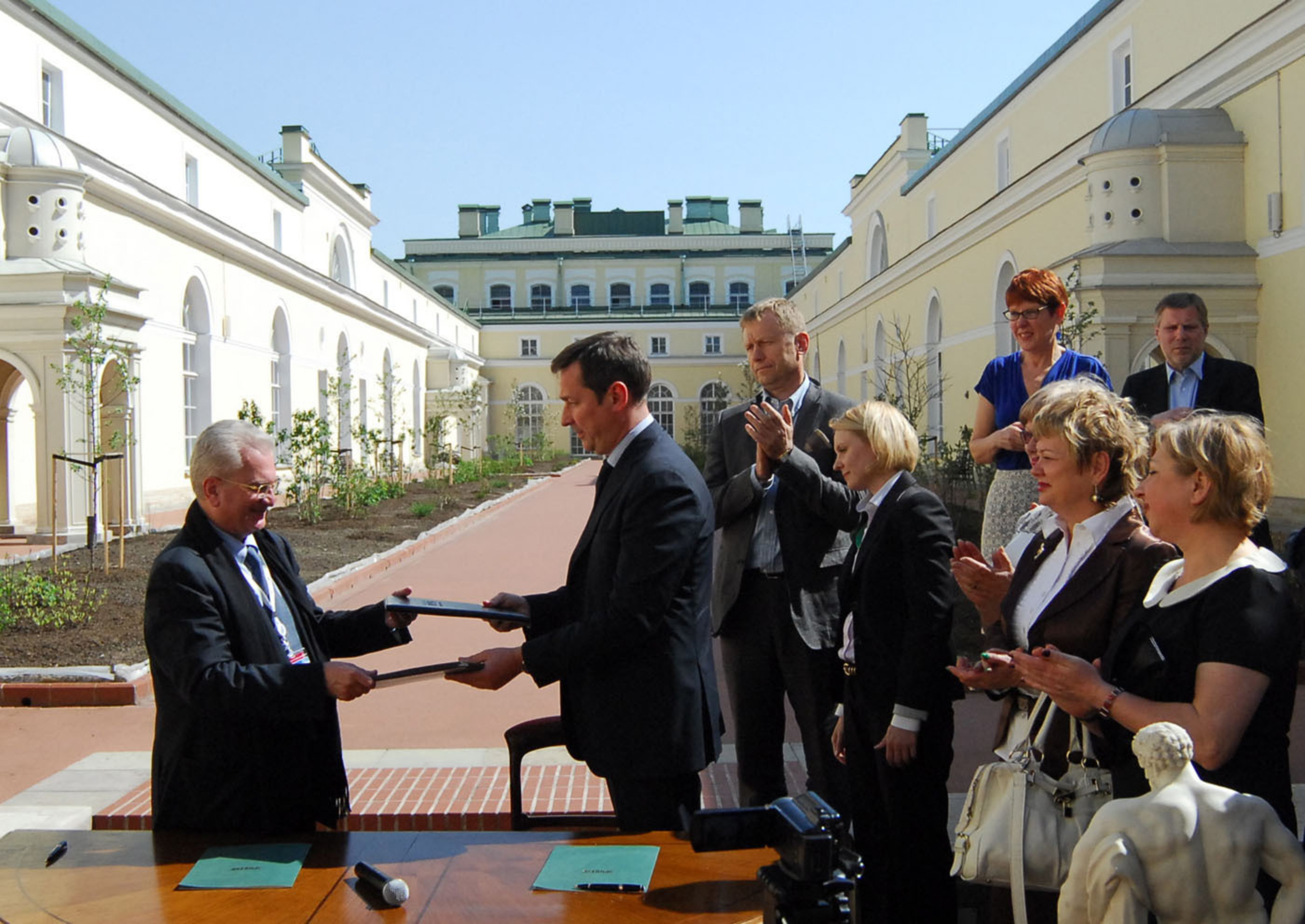 """Mayor Arturas Zuokas of Vilnius, Lithuania (center) and Dr. Mikhail Piotrovsky, Director of the State Hermitage Museum sign an Agreement for Cooperation in St. Petersburg, Russia applauded by Lithuanian Minister of Culture Sarunas Birute and members of the Vilnius City Council in St. Petersburg, Russia. The exhibition """"FLUXUS: Russian Atlases"""" by the founder of the FLUXUS movement, Lithuanisn George Maciunas, will open on September 20th at the Hermitage. It will also showcase visual works by legendary Lithuanian avant garde filmmaker Jonas Mekas from New York. (PRNewsFoto/Jonas Mekas Foundation USA) (PRNewsFoto/JONAS MEKAS FOUNDATION USA)"""