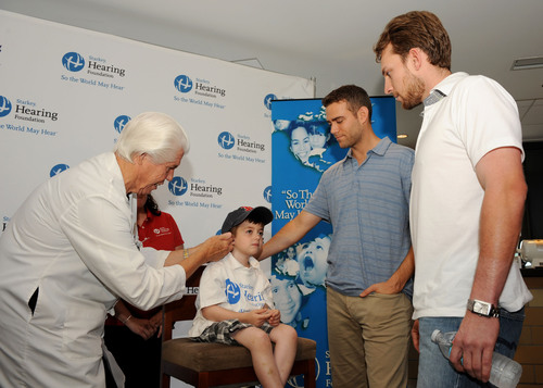 Boston Red Sox Shortstop Jed Lowrie (right) and General Manager Theo Epstein (center) join Bill Austin, Founder of the Starkey Hearing Foundation (left) as they provide the gift of hearing to a patient at the Starkey Hearing Foundation Boston Mission. More than 60 children and adults were fitted with a custom-made hearing aid at Fenway Park.(PRNewsFoto/Starkey Hearing Foundation)