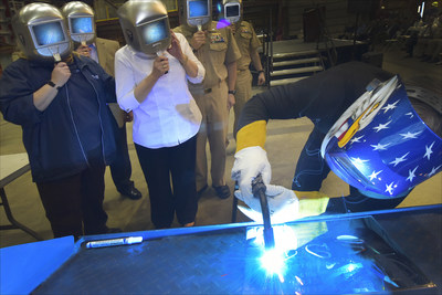 A welder authenticates the keel by welding the initials of LCS 15 sponsor Sharla Tester onto the keel plate. The Keel Laying is the formal recognition of the start of the ship's module construction process. Photo credit: Joseph Mancini, Lockheed Martin.