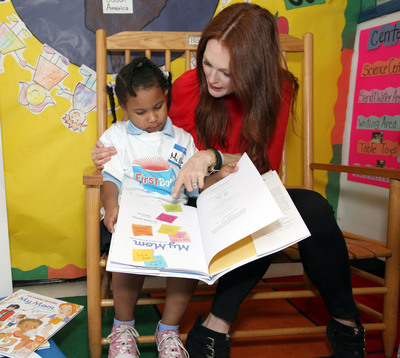 Children's author and award-winning actress Julianne Moore reading her new book with a child at a community center in Harlem to celebrate the start of a new school year. Moore appeared at Round the Clock Nursery with Kyle Zimmer, president and CEO of First Book, a nonprofit social enterprise that provides new books and educational materials for kids in need. Moore read from her new book, 'My Mom is a Foreigner, But Not to Me' to pre-K students and their parents, and gave each participating child a signed copy of the book.  (PRNewsFoto/First Book)