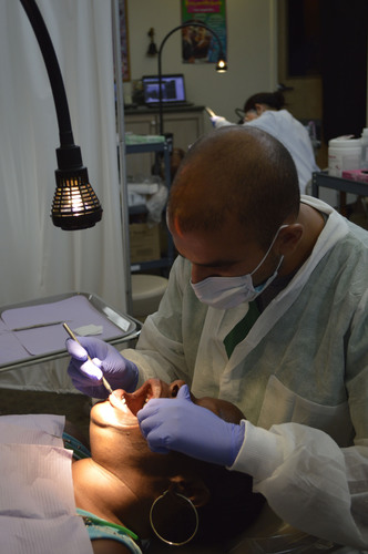 Louise Edwards, of Detroit, participates in the free dental care services offered during the launch of the ...