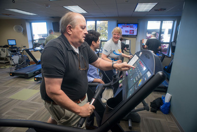 Marcus Dobson (foreground) of Clemmons, N.C., adjusts his machine while Bunny Fontrier (rear) of Winston-Salem, N.C., chats with staff member Hector Hernandez Saucedo during an exercise session at Wake Forest Baptist Medical Center's Sticht Center for Aging.  (PRNewsFoto/Wake Forest Baptist HealthWire)