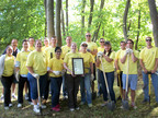 """EY Stamford professionals holding the mayoral proclamation of """"EY Connect Day"""" while volunteering at Stamford Museum & Nature Center"""