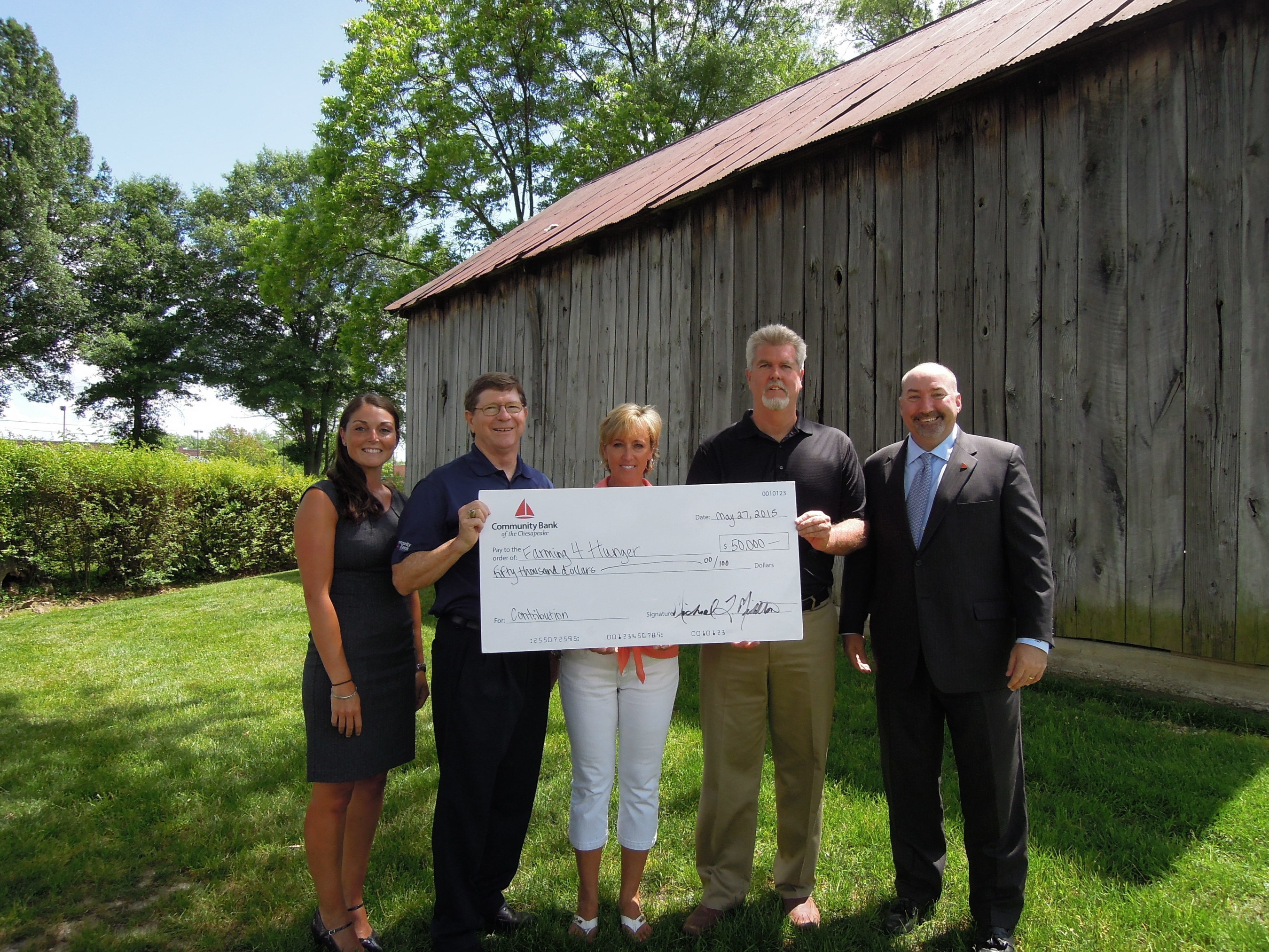 Community Bank of the Chesapeake representatives present the donation check to Farming 4 Hunger. Pictured from left to right: Lacey Pierce, Senior Vice President, Senior Lender for Community Bank of the Chesapeake; Michael Middleton, Executive Chairman of the Board of Directors for Community Bank of the Chesapeake; Farming 4 Hunger treasurer Rose Torboli and founder Bernie Fowler; and Don Parsons, Jr., Senior Vice President, Senior Lender with Community Bank of the Chesapeake.