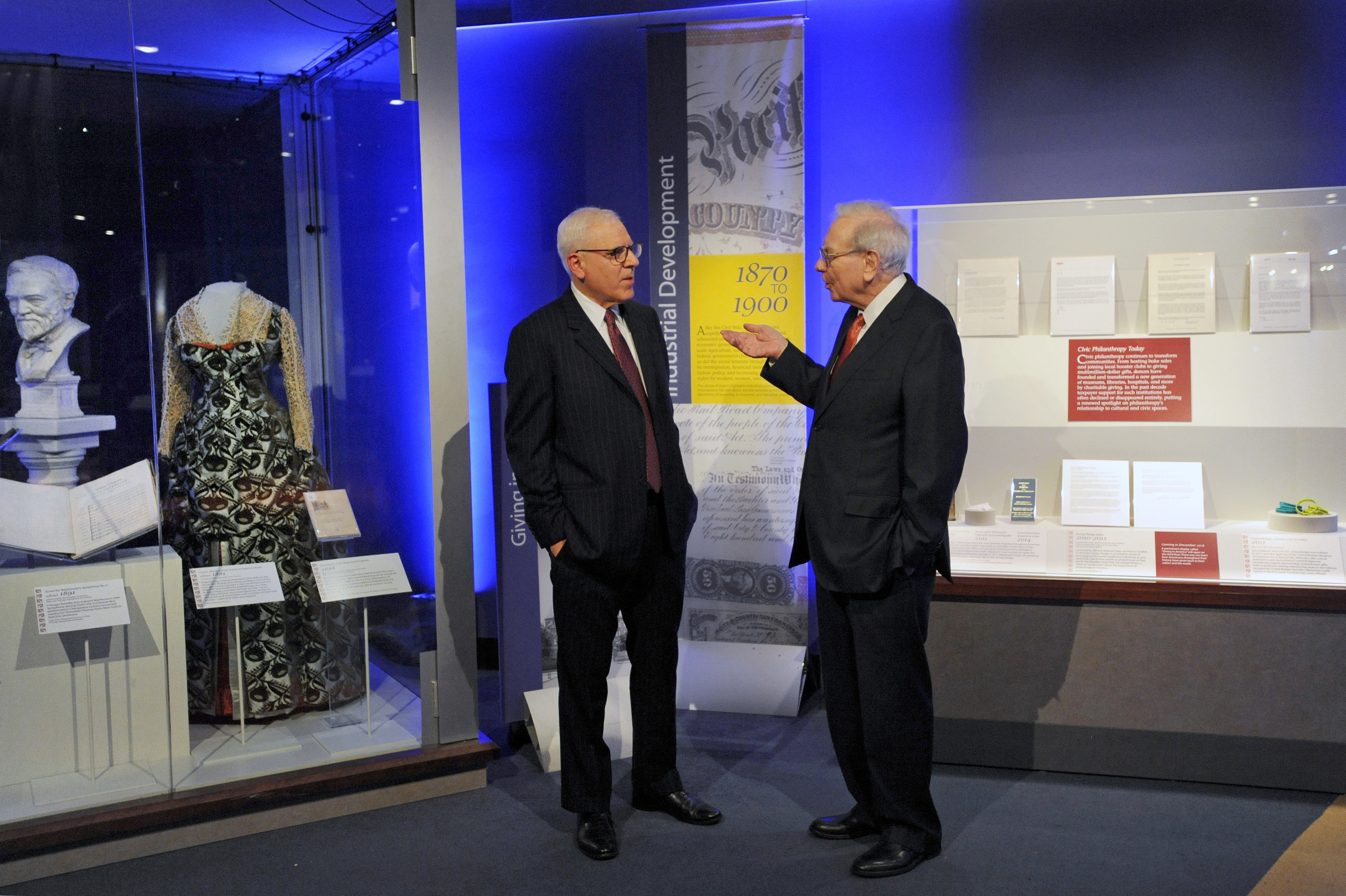 "David Rubenstein, co-CEO, The Carlyle Group and Chair, Smithsonian Board of Regents and Warren Buffett, chairman and CEO, Berkshire Hathaway Inc. preview the ""Giving in America' display at the National Museum of American History. The cases, which open to the public Dec. 1, examine philanthropy in two American eras, the Gilded Age and today."