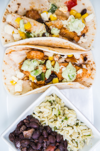 Zona Cocina fresh flavorful food: Blackened Mahi Tacos, twin flour or corn tortillas with roasted corn and black bean relish and avocado creme, with black beans and rice. (PRNewsFoto/AIRMALL USA)