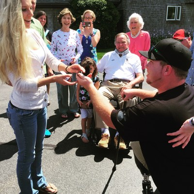 "Tyler Jeffries, one of ten veterans featured in the book ""Unbreakable Bonds: The  Mighty Moms and Wounded Warriors of Walter Reed,"" proposes to Lauren Lilly during a visit with Presidents George H.W. Bush and George W. Bush and First  Ladies Barbara Bush and Laura Bush at Walker's Point in Kennebunkport, Maine.  President Bush 41 wrote the foreword for ""Unbreakable Bonds"" and had invited the wounded  warriors, their moms, and the book's authors, Dava Guerin and Kevin Ferris, to visit with the family on Aug. 10, 2015."