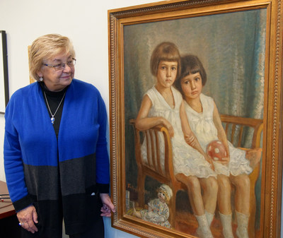 Susan Mikula, Ph.D., acting dean of the College of Liberal Arts at Benedictine University in Lisle, Illinois, stands next to a 1928 oil painting of her mother and aunt that hangs in her office.