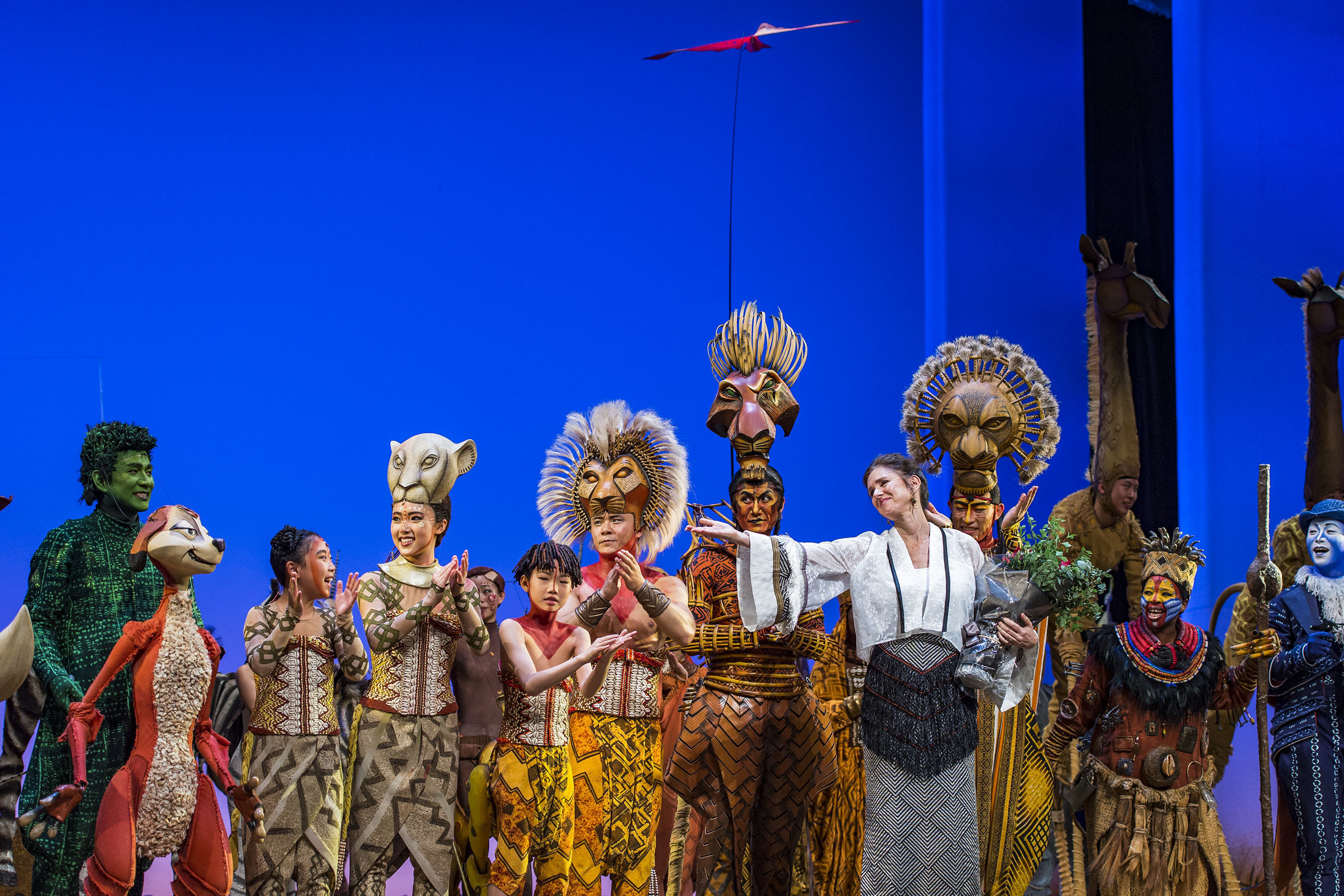 The cast of Disney's THE LION KING honors Broadway director Julie Taymor during the Global Premiere of the first-ever production in Mandarin at the Grand Opening of Shanghai Disney Resort. Taymor, the director, costume designer and co-mask designer of the original Broadway production, was on hand to celebrate the opening of this historic show, staged exclusively at the Walt Disney Grand Theatre in Disneytown at the Resort. In its 19th year, THE LION KING remains ascendant as one of the most popular stage musicals in the world. Since its Broadway premiere on November 13, 1997, 22 global productions have been seen by more than 85 million people and, cumulatively, run a staggering 132 years.
