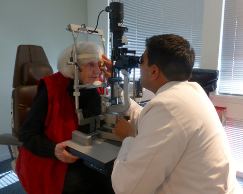 A patient with age-related macular degeneration receives an eye exam from her ophthalmologist. ...